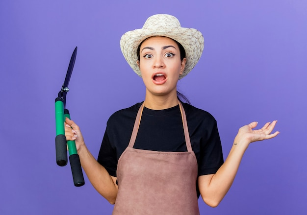 Jovem e bela jardineira de avental e chapéu segurando uma tesoura de cerca-viva parecendo surpresa e maravilhada de pé sobre a parede azul