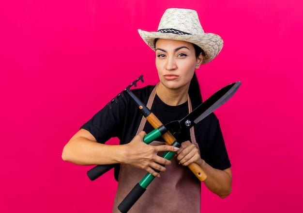 Jovem e bela jardineira de avental e chapéu segurando uma tesoura de sebes e um mini ancinho olhando para a frente com uma cara séria em pé sobre a parede rosa
