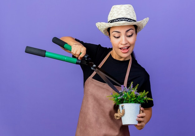Jovem e bela jardineira de avental e chapéu segurando uma tesoura de sebes e vasos de plantas sorrindo em pé sobre a parede azul