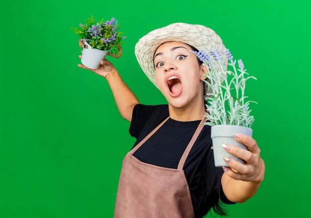 Jovem e bela jardineira de avental e chapéu segurando vasos de plantas olhando gritando em pé sobre um fundo verde