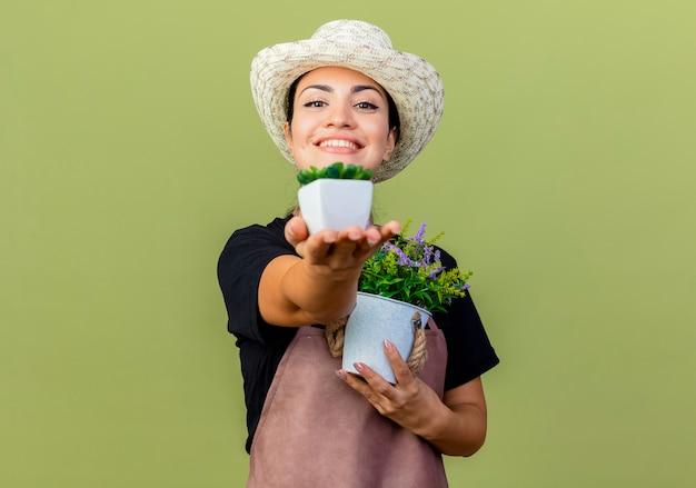 Jovem e bela jardineira de avental e chapéu segurando vasos de plantas olhando para a frente, sorrindo alegremente em pé sobre a parede verde claro
