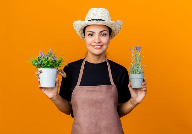 Jovem e bela jardineira de avental e chapéu segurando vasos de plantas olhando para a frente sorrindo com uma cara feliz em pé sobre a parede laranja