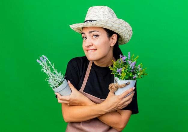 Jovem e bela jardineira de avental e chapéu segurando vasos de plantas olhando para a frente, sorrindo e ficando confusa em pé sobre a parede verde