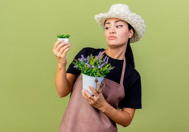 Jovem e bela jardineira de avental e chapéu segurando vasos de plantas, parecendo confusa, tentando fazer uma escolha em pé sobre uma parede verde claro