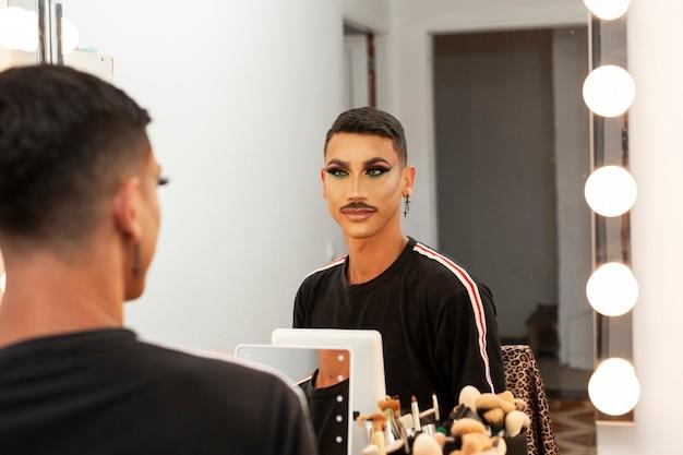 Jovem e bela maquiadora drag queen se olhando em frente ao espelho