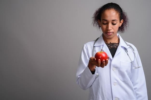 Jovem e bela médica africana contra uma parede cinza
