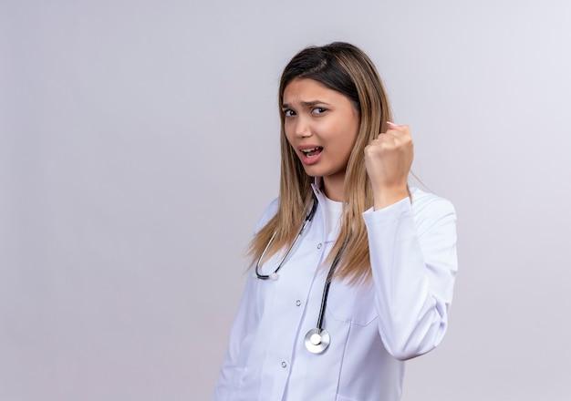 Jovem e bela médica vestindo jaleco branco com estetoscópio cerrando o punho com cara de zangado