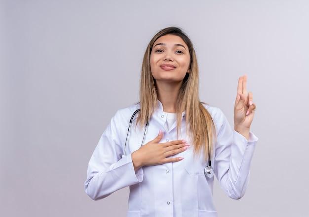 Jovem e bela médica vestindo jaleco branco com estetoscópio levantando a mão para prestar juramento parecendo confiante