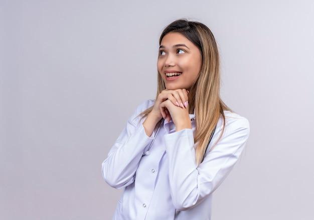 Jovem e bela médica vestindo jaleco branco com estetoscópio olhando para o lado de mãos dadas e esperando pela surpresa
