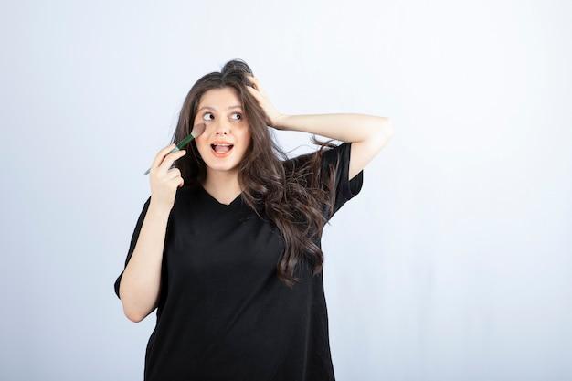 Jovem e bela modelo aplicando blush com pincel na parede branca.