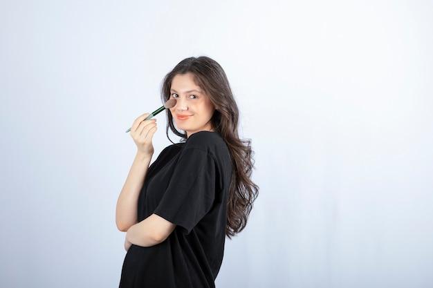 Jovem e bela modelo aplicando sombra com pincel na parede branca.
