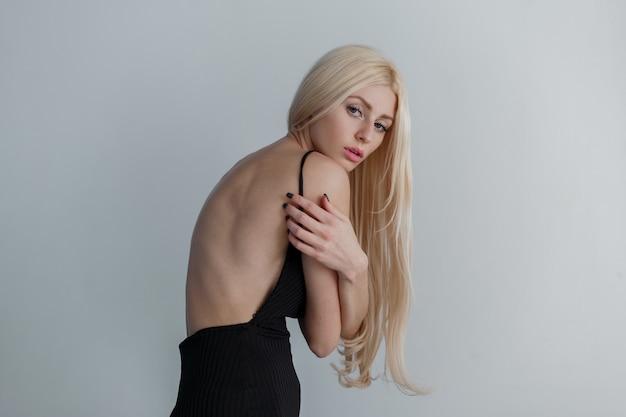 Jovem e bela modelo mulher com sardas em roupas pretas e costas nuas posando perto da parede cinza