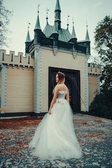 Jovem e bela modelo posando com um longo vestido de marfim no jardim com uma coroa na cabeça