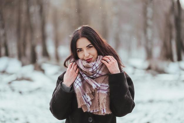Jovem e bela modelo posando na floresta de inverno.