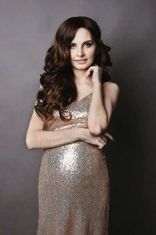 Jovem e bela morena grávida com maquiagem suave, com o vestido dourado brilhante, sorrindo e posando para o fundo cinza
