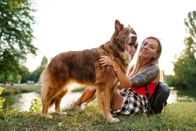 Jovem e bela mulher acariciando seu cachorro fofo no parque, close-up
