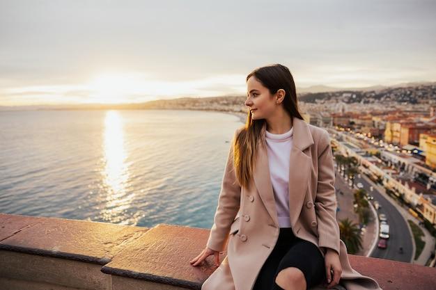 Jovem e bela mulher admirando a vista panorâmica de uma rua europeia em nice, frança, no pôr do sol.