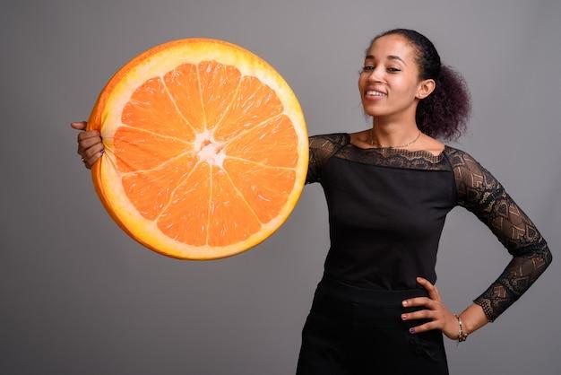 Jovem e bela mulher africana em cinza