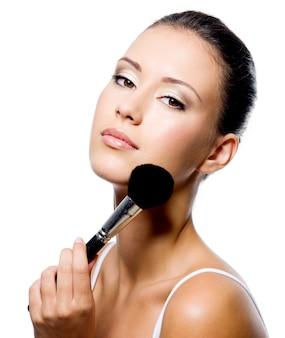 Jovem e bela mulher aplicando pó na maçã do rosto com pincel - isolado