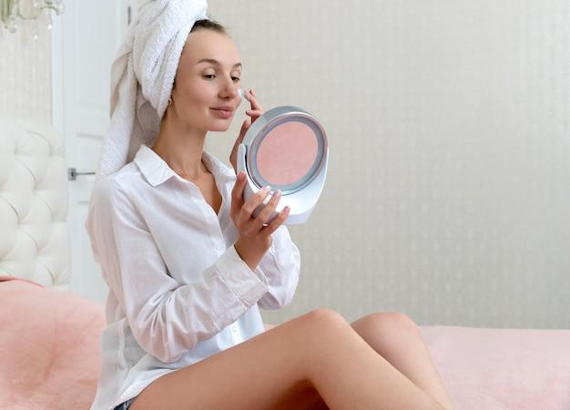 Jovem e bela mulher aplicar máscara facial no quarto
