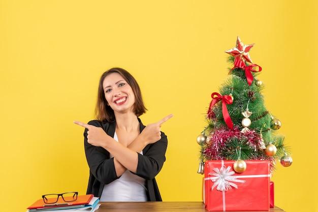 Jovem e bela mulher apontando algo em diferentes direções, sentado em uma mesa perto da árvore de natal decorada no escritório em amarelo