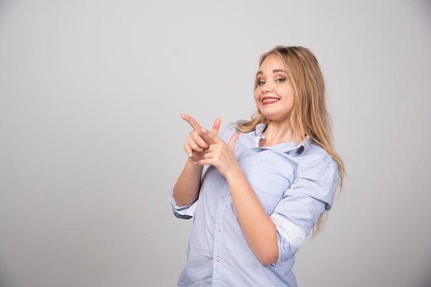 Jovem e bela mulher apontando com duas mãos e dedos para o lado.
