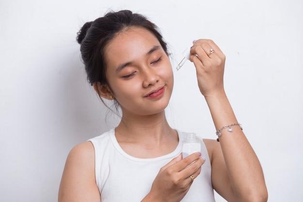 Jovem e bela mulher asiática aplicando soro hidratante no rosto, isolado no fundo branco