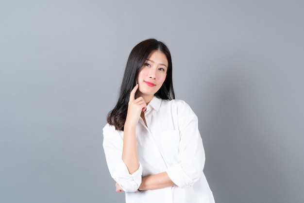 Jovem e bela mulher asiática com uma cara feliz e pensando em uma camisa branca na parede cinza