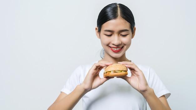 Jovem e bela mulher asiática comendo hambúrguer, sentindo-se feliz, olha para o hambúrguer.