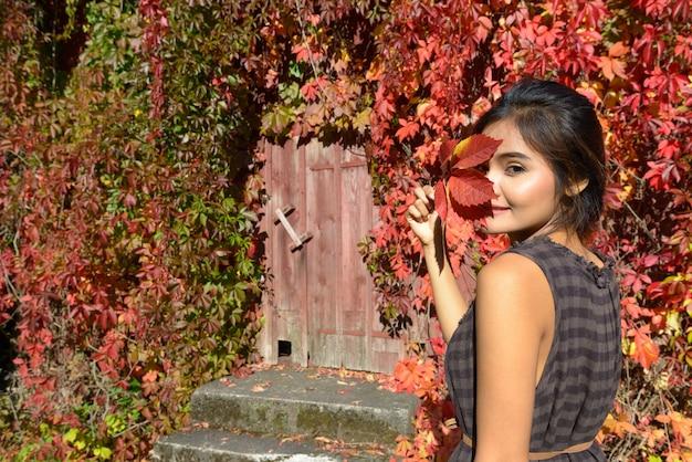 Jovem e bela mulher asiática contra uma casa suburbana coberta de folhas de outono