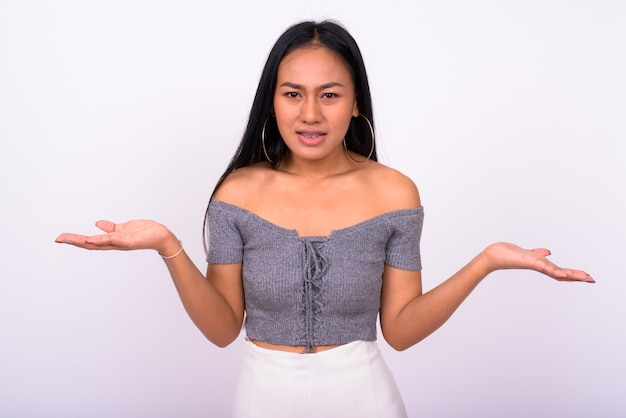 Jovem e bela mulher asiática contra uma parede branca