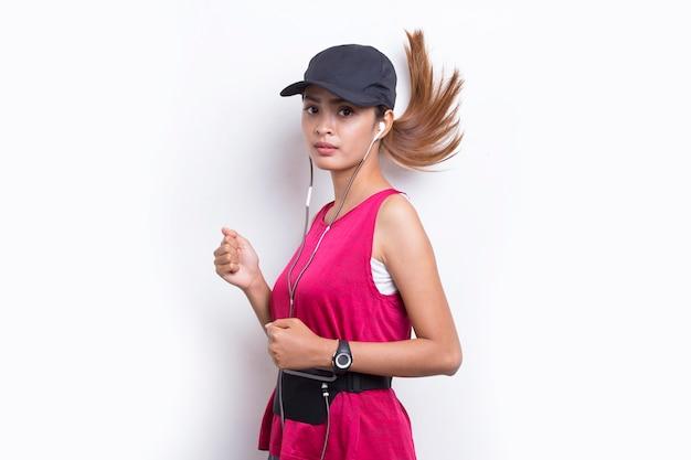Jovem e bela mulher asiática desportiva correndo em fundo branco