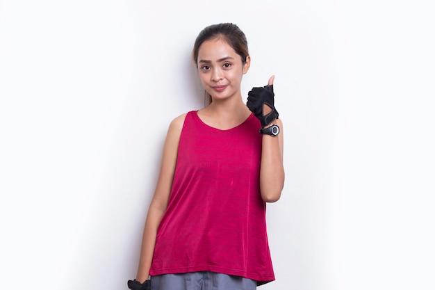 Jovem e bela mulher asiática desportiva mostrando um gesto de ok com o polegar para cima no fundo branco