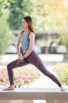 Jovem e bela mulher asiática em roupas esportivas, fazendo alongamento antes dos exercícios no calor durante a pandemia de covid-19 para manter uma vida saudável. mulher jovem saudável se alongando e se preparando para os treinos