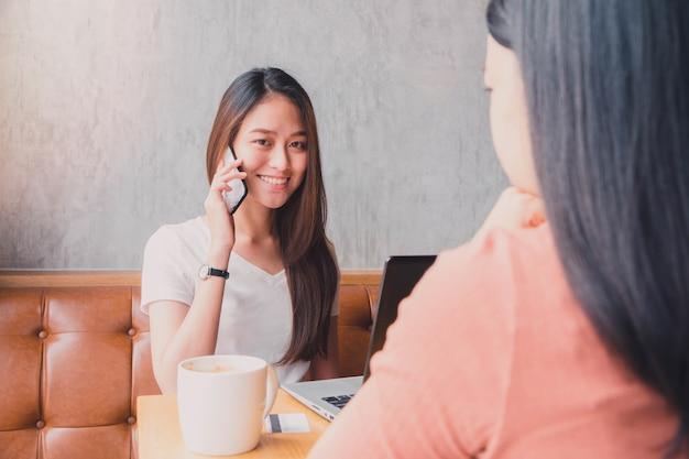 Jovem e bela mulher asiática trabalhando e falando com telefone inteligente no fundo do café