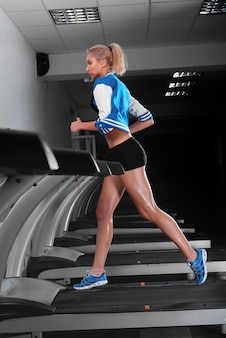 Jovem e bela mulher atlética correndo em uma esteira na academia