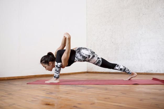 Jovem e bela mulher atlética praticando ioga interior no tapete vermelho