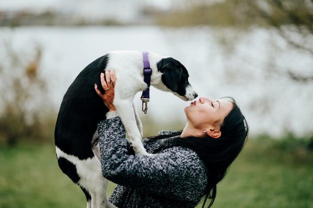 Jovem e bela mulher beijando o cachorro ao ar livre.