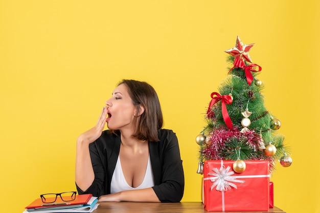 Jovem e bela mulher bocejando sentada em uma mesa perto da árvore de natal decorada no escritório em amarelo