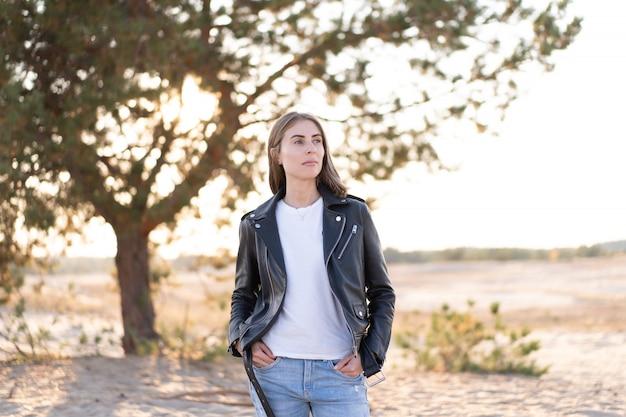 Jovem e bela mulher caucasiana vestida de jeans e jaqueta de couro fica na praia os raios do sol romper a folhagem de uma árvore