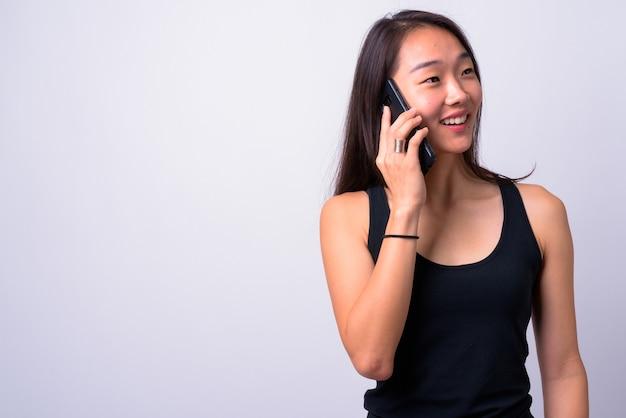 Jovem e bela mulher chinesa contra uma parede branca