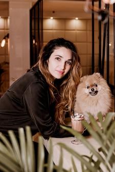 Jovem e bela mulher com seu cachorro da pomerânia em um café