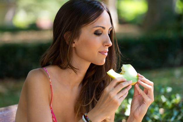 Jovem e bela mulher comendo pedaço de melão no jardim.