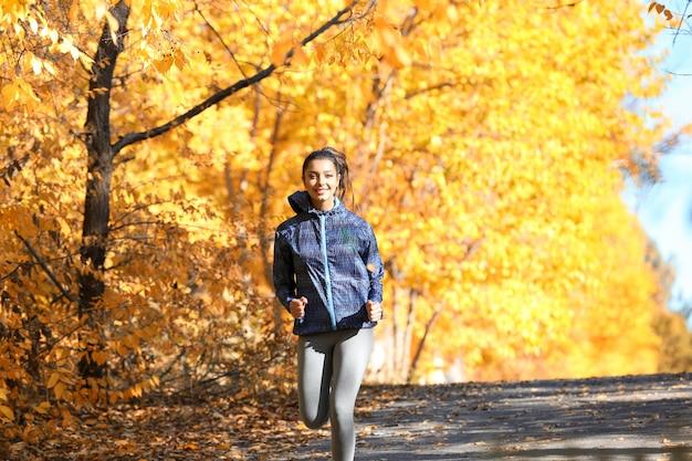 Jovem e bela mulher correndo no parque outono