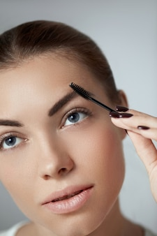 Jovem e bela mulher corrigindo a forma das sobrancelhas. maquiagem de contorno de sobrancelha.