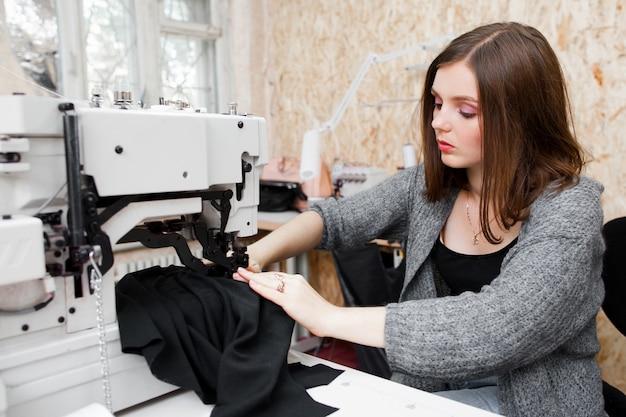 Jovem e bela mulher costurando na máquina.