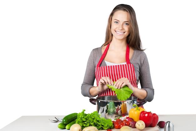 Jovem e bela mulher cozinhando em fundo branco