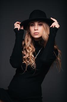 Jovem e bela mulher de chapéu preto sentada na parede preta