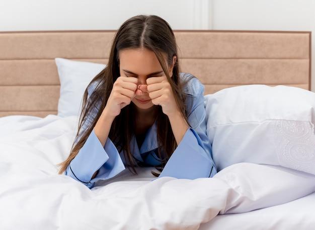 Jovem e bela mulher de pijama azul deitada na cama, esfregando os olhos, bocejando, sentindo o cansaço matinal no interior do quarto com luz de fundo