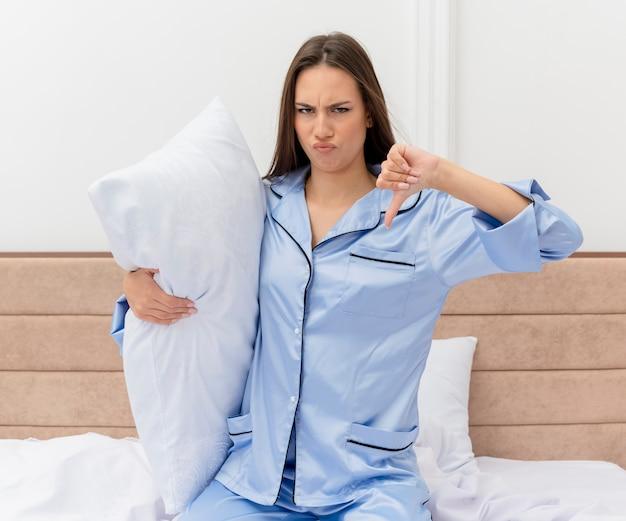 Jovem e bela mulher de pijama azul, sentada na cama com o travesseiro desgostoso, mostrando os polegares para baixo no interior do quarto